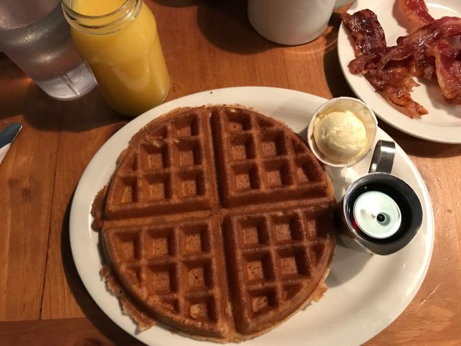 Waffle on plate with butter and maple syrup. Bacon is on another plate, and a glass of orange juice is at the top left of the image.