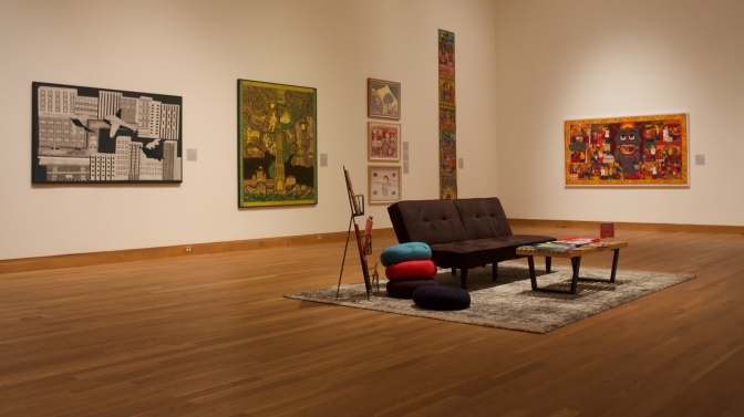 Gallery of Indian art. A couch, a coffee table, cushions, and art books are in the middle of the room.