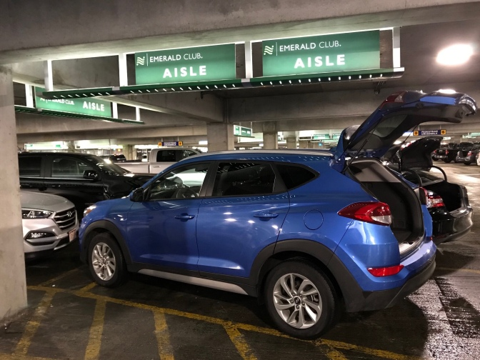 Blue Hyundai Tuscon in parking garage, signs above that says EMERALD CLUB AISLE.
