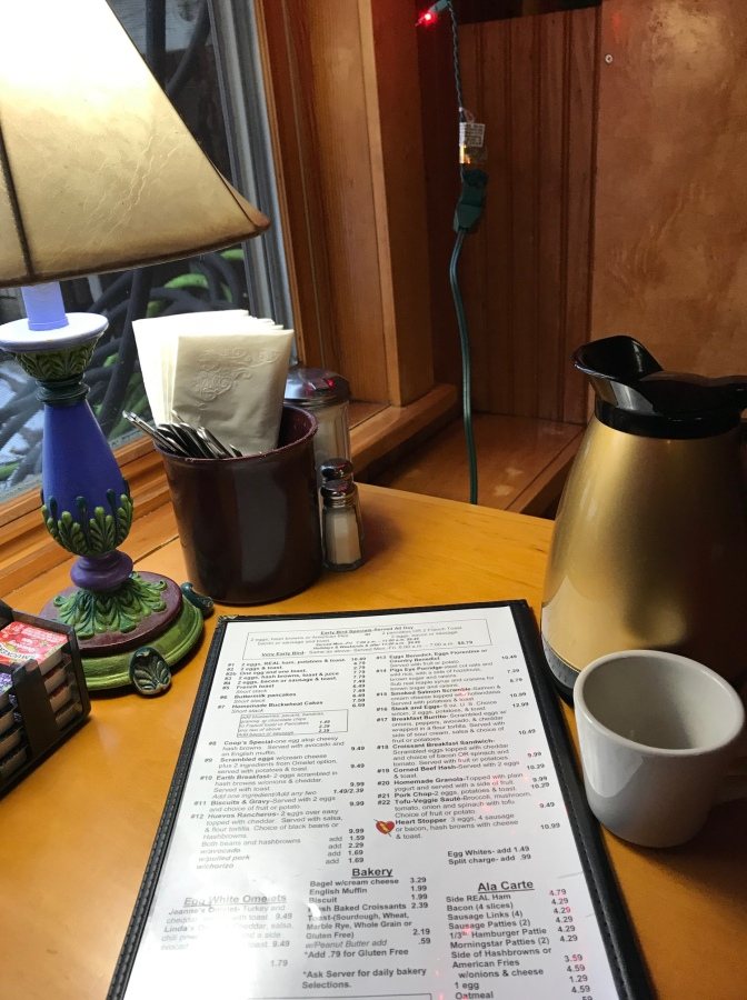 Table at restaurant with pot of coffee, coffee cup, menu, lamp, and cup with napkins and flatware.