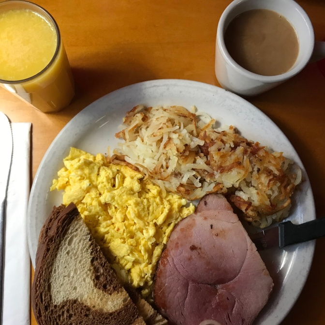 Plate with scrambled eggs, ham, hashed browns, and rye toast. A cup of coffee and a glass of orange juice is on the table.