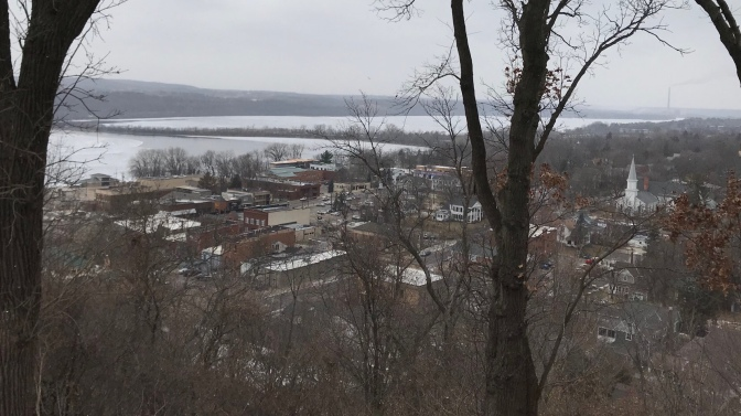 Trees in foreground, with town of Hudson at a lower elevation.