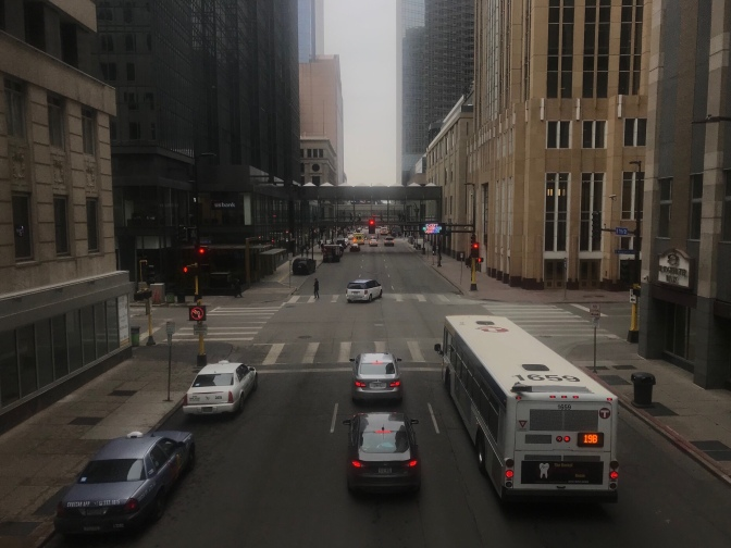 View of skyways from inside a skyway. Buses and cars are in the streets below.