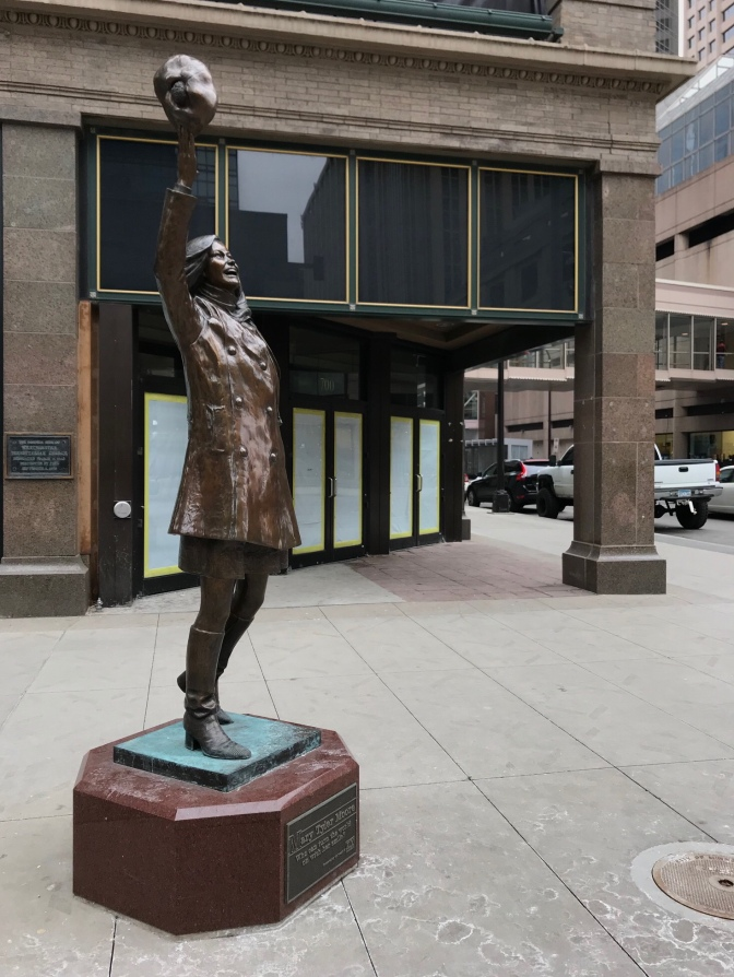 Statue of Mary Tyler Moore on pedestal in front of brick building.