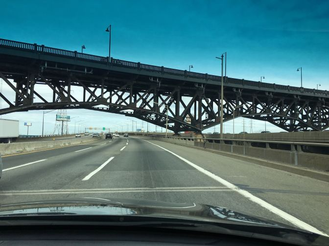 View of NJ Turnpike. A large metal bridge crosses the roadway.