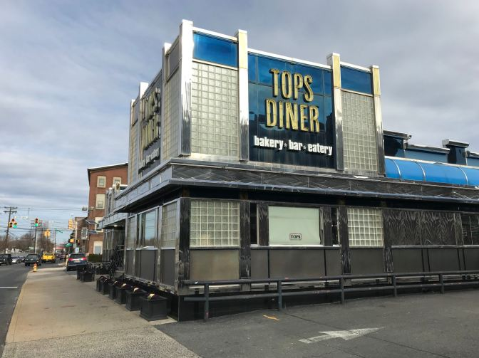 Photo of exterior of TOPS DINER. Sign on side of building says TOPS DINER BAKERY BAR EATERY.