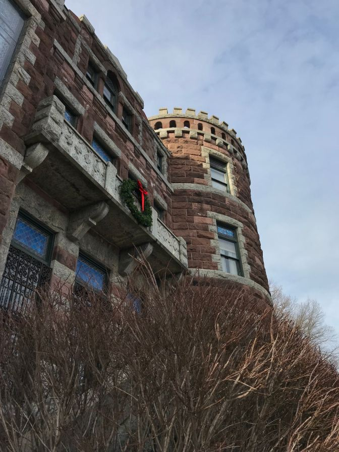Exterior of castle, looking at three-story turret. Bare branches of a bush are in the foreground.