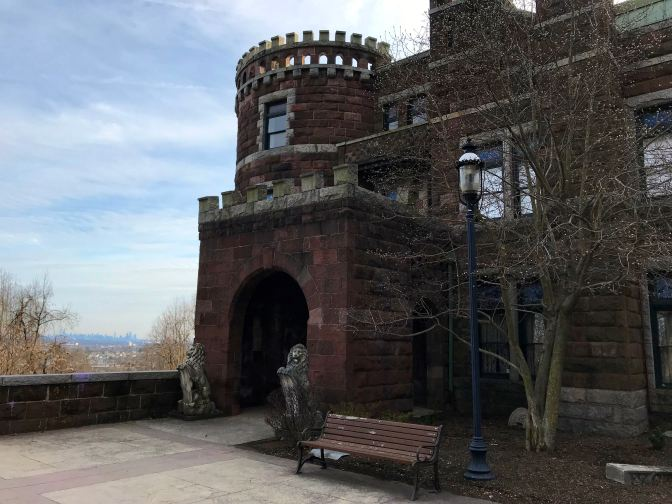 View of entrance to Lambert Castle, with skyline of New York in the distance.