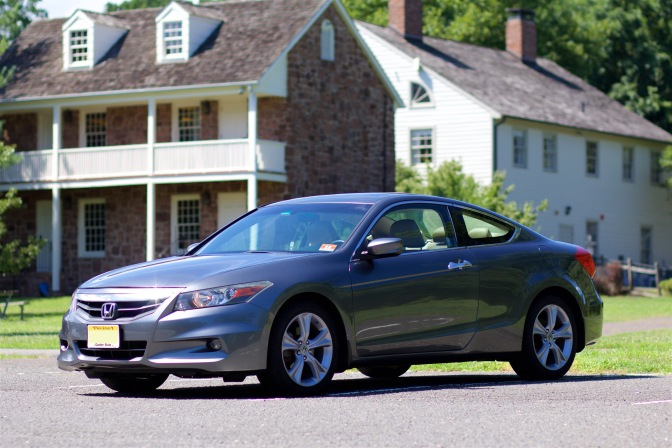 Side view of 2012 Honda Accord coupe, in gray ,with buildings in the background.