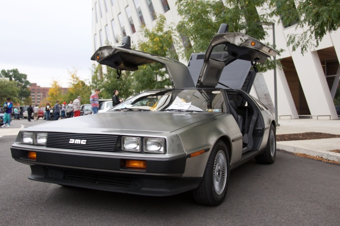 Silver Delorean DMC with its doors raised.