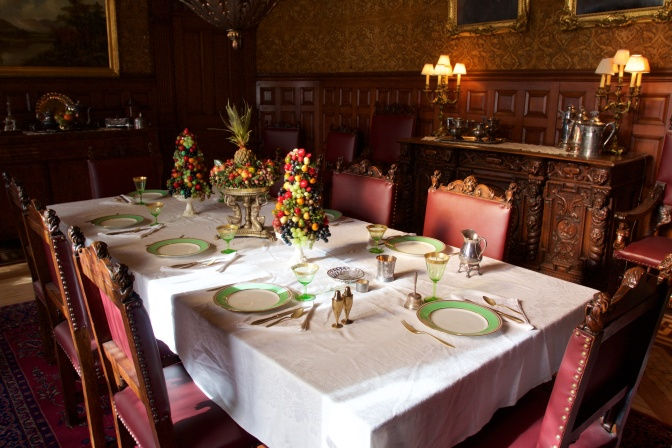 Dining room of the castle. The large rectangular table has places set for 8 people, with gold flatware and white plates with gold rims. There are three centerpieces made of fruit, and a sideboard holds water tankards and lights.