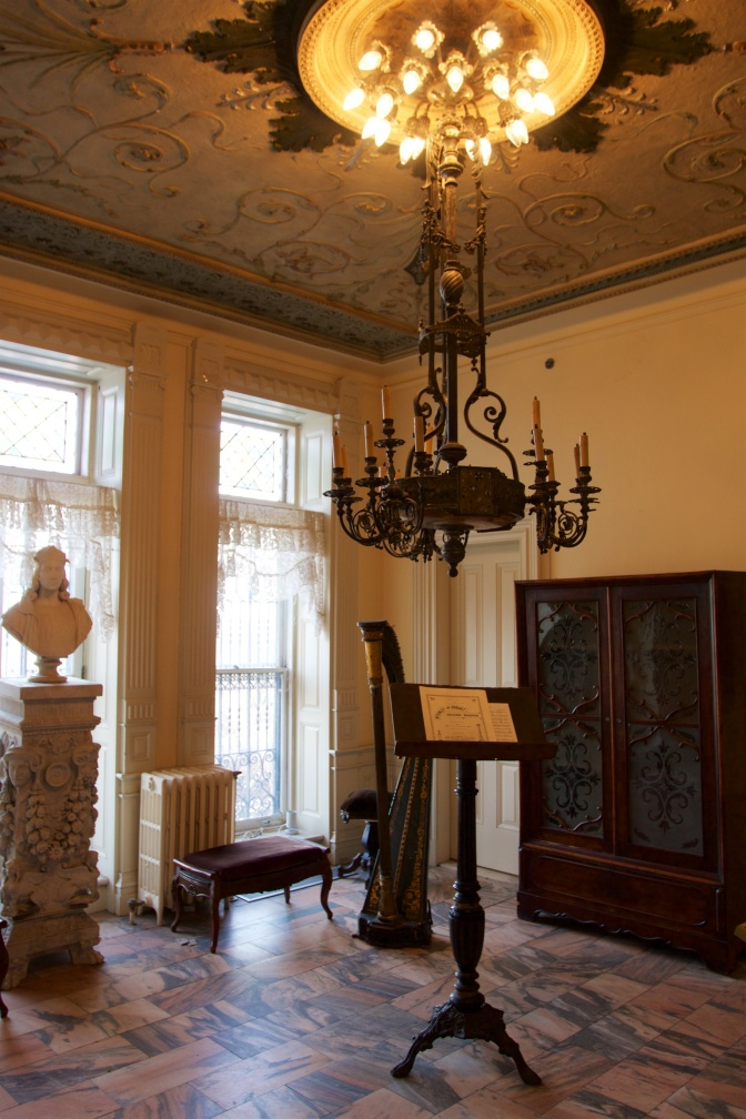 Music room, with bust on pedestal, hanging chandelier, harp, bench, and music stand.