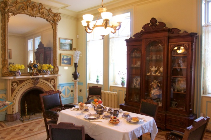 Breakfast room, with a table set for four, a large mirror over the fireplace, and a sideboard filled with tea sets and plate sets.
