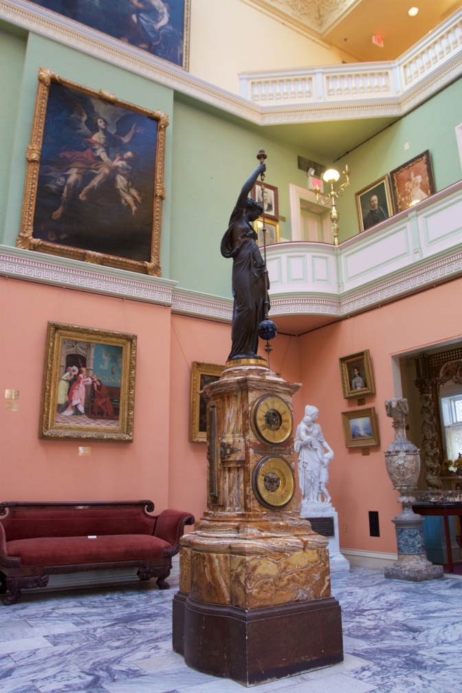 Grand Atrium, with a large clock statue in the middle of the floor, and paintings on the wall.