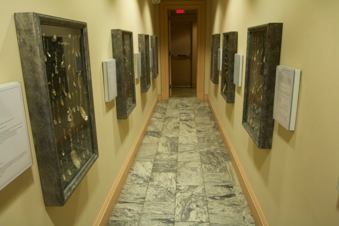 Hallway with spoons displayed in cases on either side.