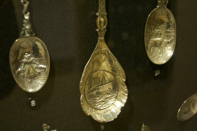 Close-up of pewter spoons with engravings. Center engraving has an ocean liner on the sea.
