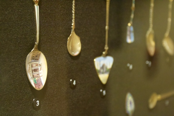 8 spoons on display in a case. The spoon on the left has an engraving of a mosque.
