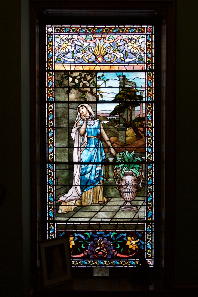 Stained glass window with woman standing on patio, a plant in a ceramic vase beside her.