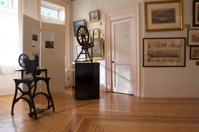 Spinning equipment on a wooden floor. Paintings hang along the walls.