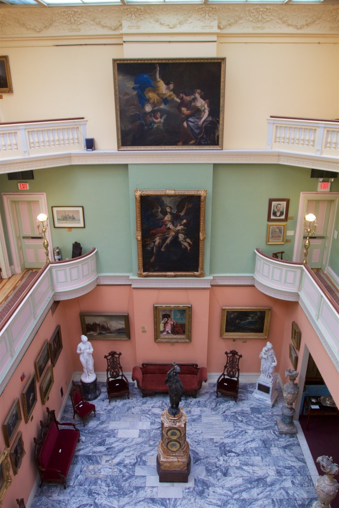 View of Grand Atrium from third floor. Paintings hang on walls, statues are on the first floor along with chairs and benches. The clock is in the center of the floor.