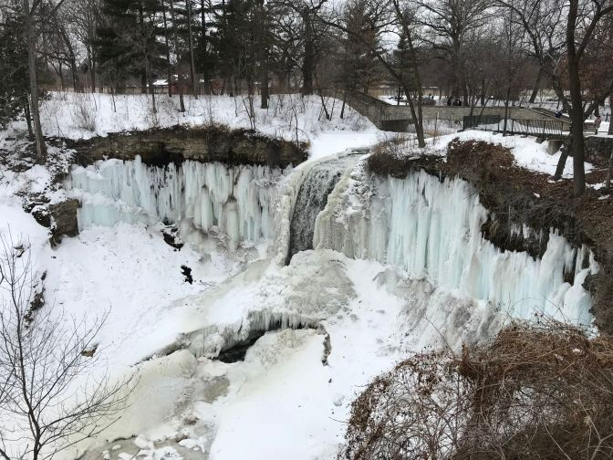 Nearly frozen Minnehaha Falls. A small channel of water runs in the middle of the falls.