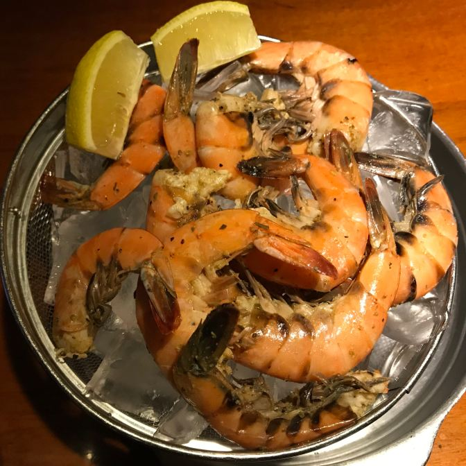 Shrimp in a bowl of ice, with lemon slices on the side.