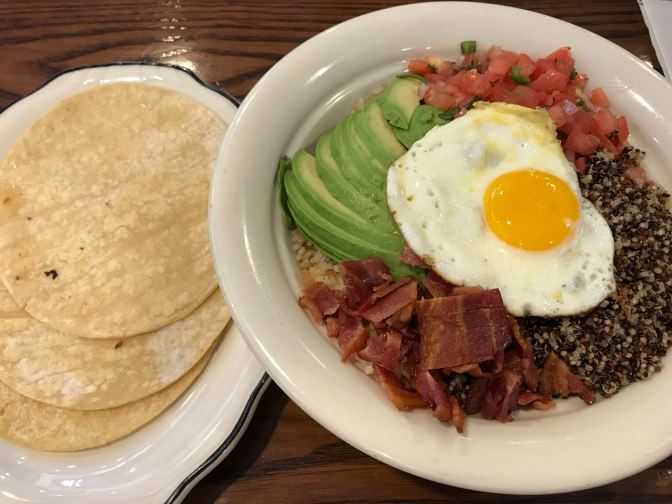 Plate on left has three corn tortillas. Plate on right has fried egg, quinoa, brown rice, tomatoes, avocado, and bacon.