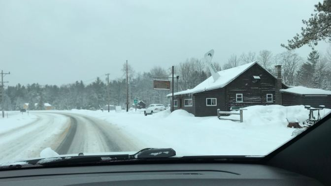 View of Wigwam Tavern on the side of a snow-covered road. View is from behind dashboard of Jeep.