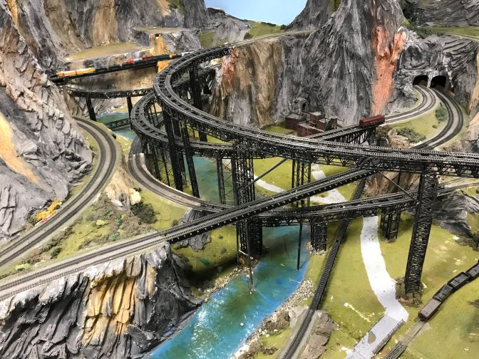 Model railroad diorama with mountains, a river, and train tracks.