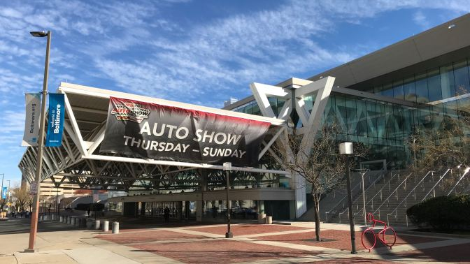 Exterior of Baltimore Convention Center, with a banner hanging that says AUTO SHOW THURSDAY - SUNDAY