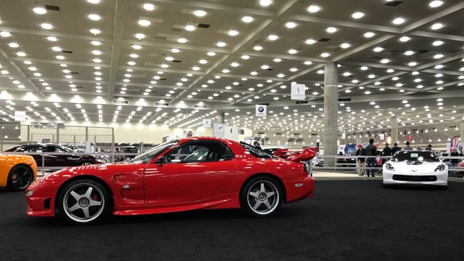 Red Mazda RX-7, with a white Corvette in the background on the right.