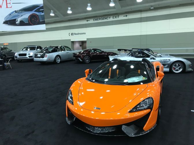 Luxury cars, with an orange McLaren in the foreground.