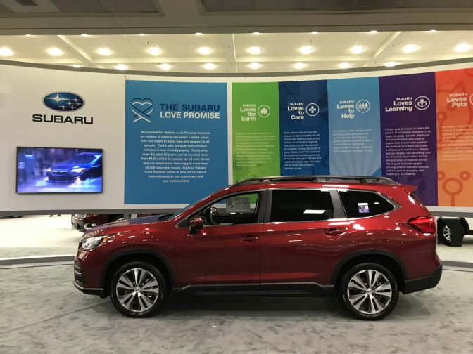 Subaru Ascent, in red in front of Subaru facade that says THE SUBARU LOVE PROMISE.