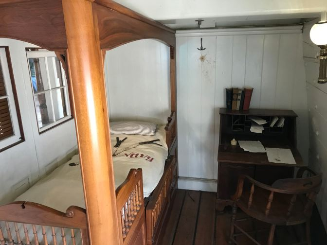 Captain's quarters, with a four-poster bed and a desk with a chair.