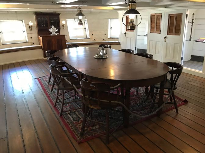 Captain's mess table, surrounded by eight chairs. White wood paneling surrounds the room.