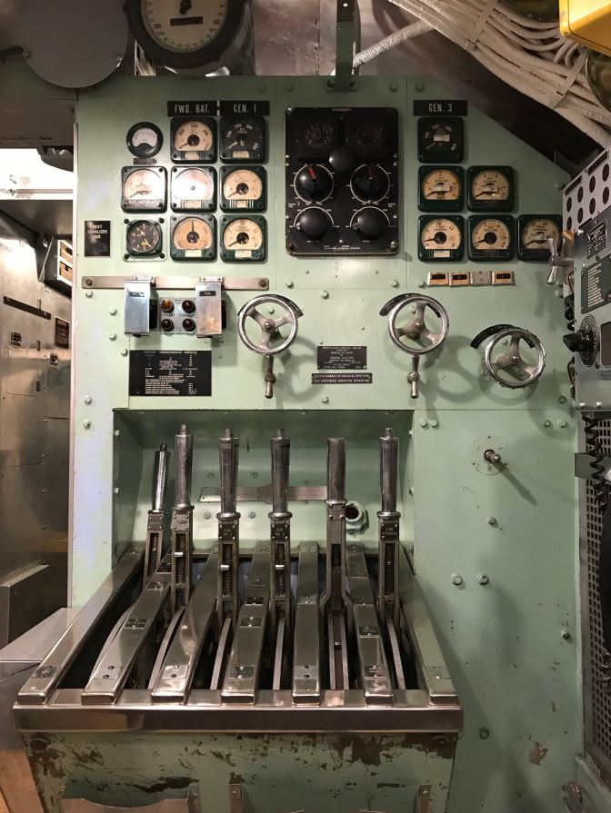 Starboard control station. Gauges are on the wall, along with dials and five levers to control speed.