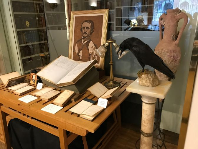 Table with books and a painting of Edgar Allan Poe. A raven doll is on a perch in the foreground.