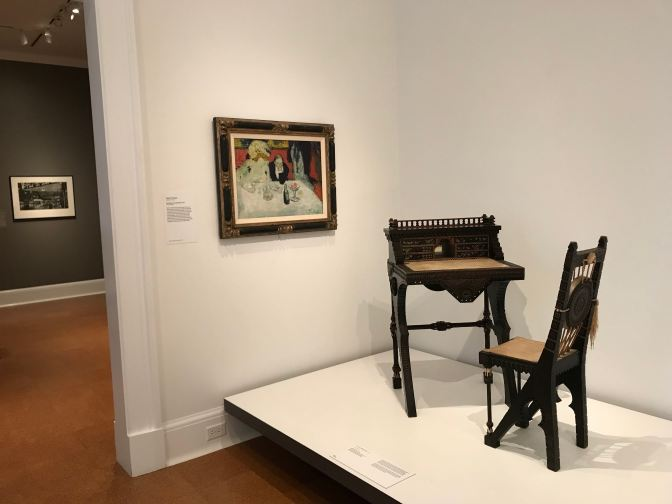 Desk and chair on a plinth in the museum, with a painting on the wall beside it.