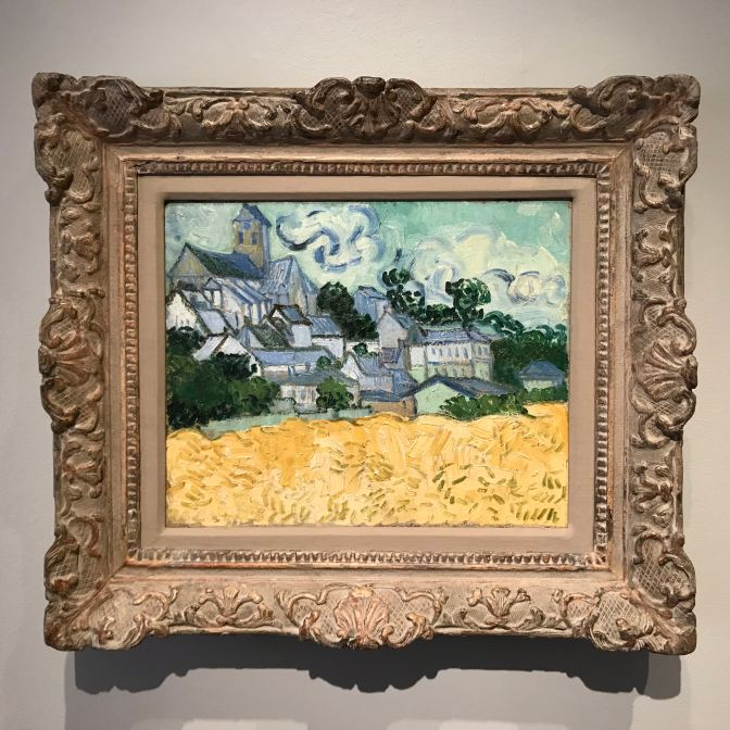 Painting by Vincent Van Gogh, View of Auvers-sur-Oise, which has a small town above a field of grain.