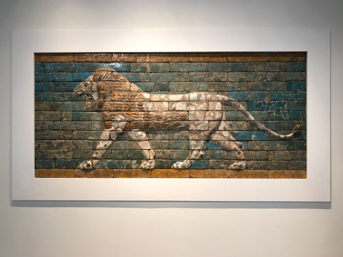 Brick mosaic of a lion on a wall.