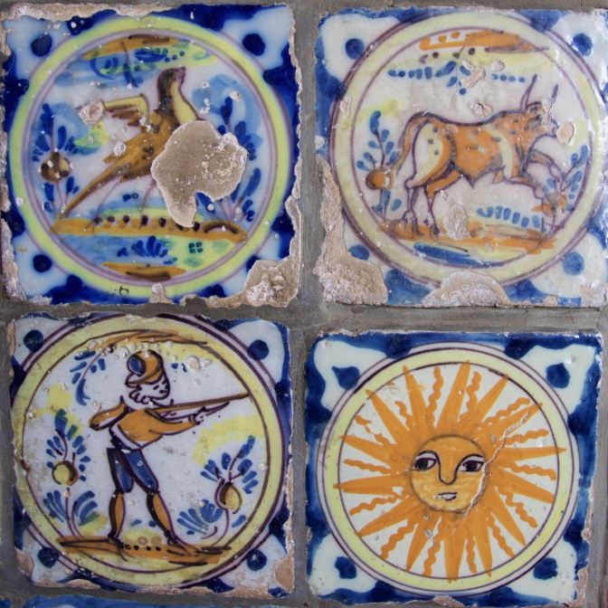 Four tiles - one of a bird, one of a cow, one of a soldiers, and one of the sun, all on a blue and white patterned background.