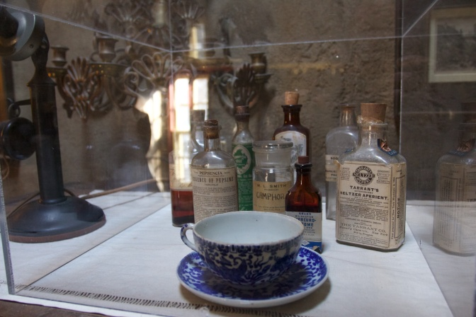 Medicines and a tea cup in a glass case.