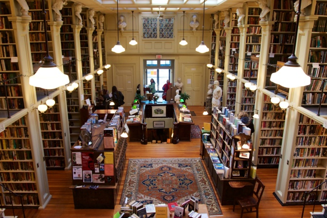 Main hall of library, with rows of bookshelves on either side of a large open area in the middle. Marble busts rest on shelves at the top of each bookshelf.