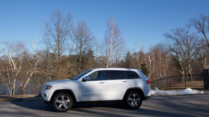 2014 white Jeep Grand Cherokee, parked in front of trees near a fence. Some snow is on the ground.