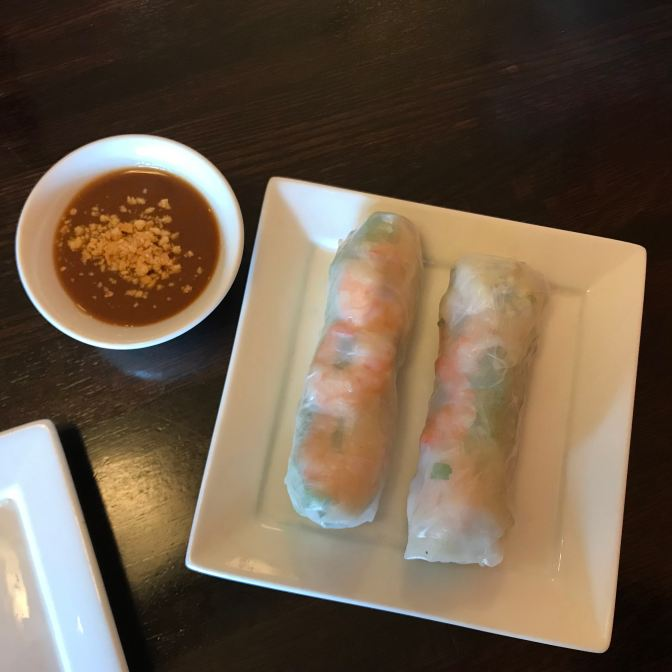 Platter with summer rolls and a small bowl with peanut sauce.
