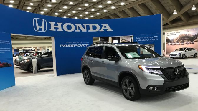 Honda Passport (silver) in front of blue facade that says HONDA - PASSPORT.