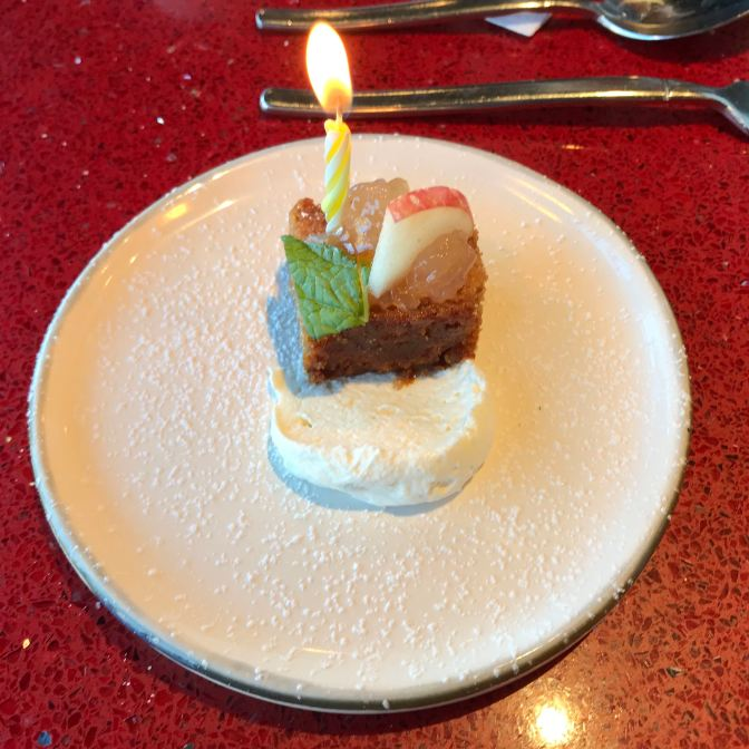 Apple cake on a white plate, with a candle in the cake.