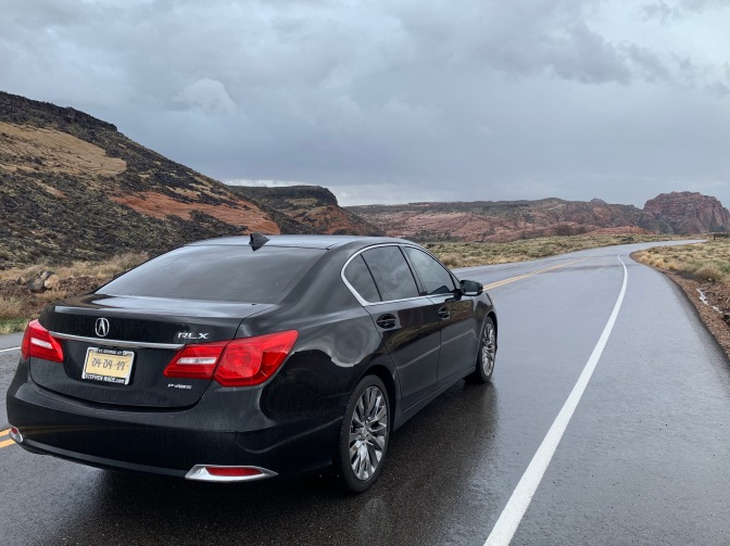 2016 Acura RLX black on rain-covered road with mountains in the background.
