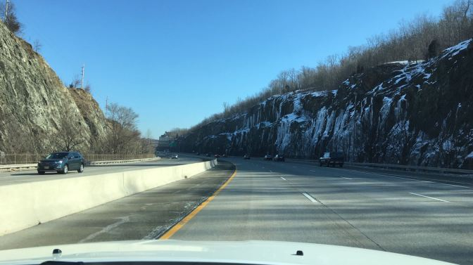 View of highway with rock cliffs on either side of the road, and ice covering the cliffs on the right.