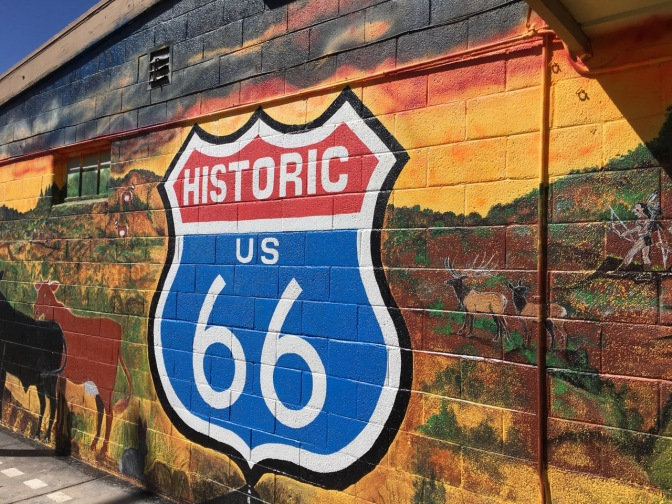 Mural of Route 66 sign on side of building with mural of Native Americans hunting bison.
